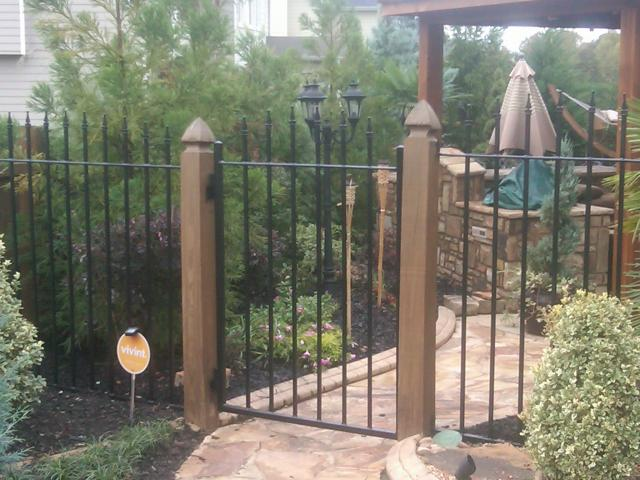 Custom wrought iron gate and fence with arched picket pattern